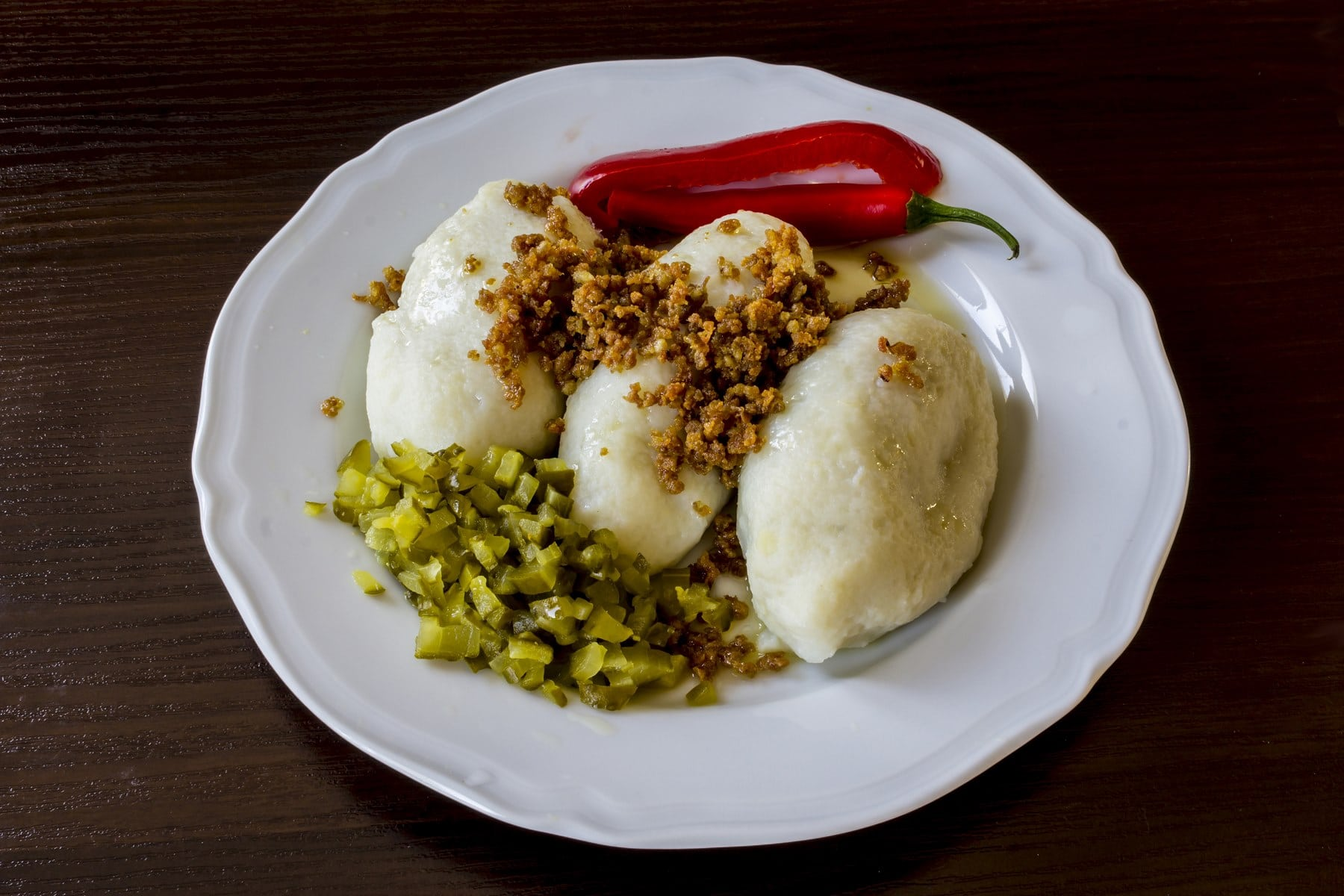 Potato dumplings - a traditional regional dish. Polish and Lithuanian cuisine. With pickles , fried bacon and paprika on a white plate on a dark background .
